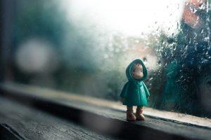 雨が降る窓際の人形