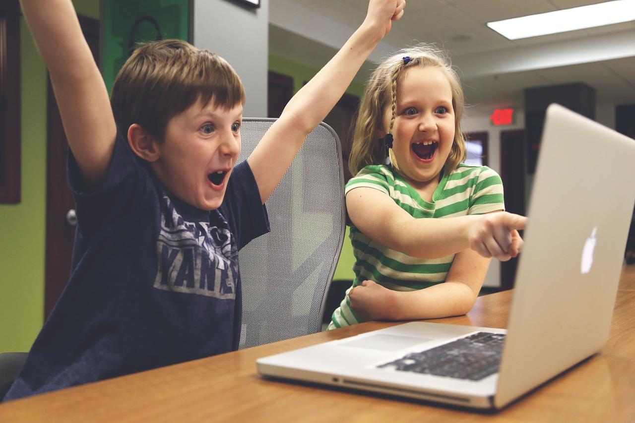 パソコンを指差し大喜びする男女の子ども