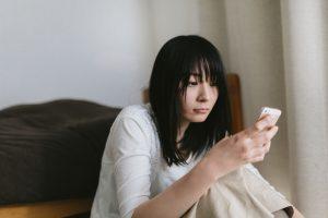 スマートフォンの画面を見て落ち込む女性