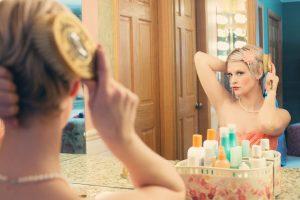 鏡を見ながら髪をとく女性