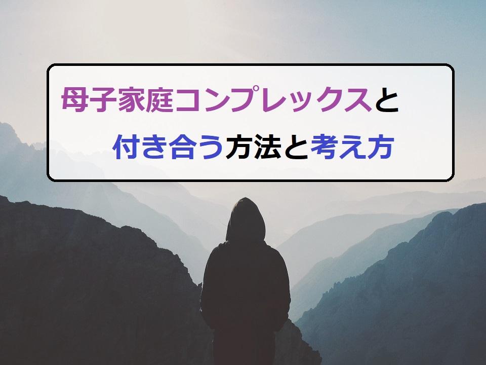 山を眺めるフードを被った人物「コンプレックス」